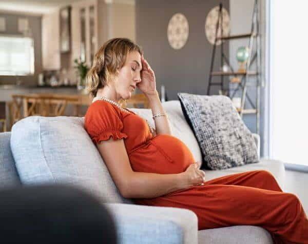 Kobieta w ciąży, cierpiąca na ból głowy.